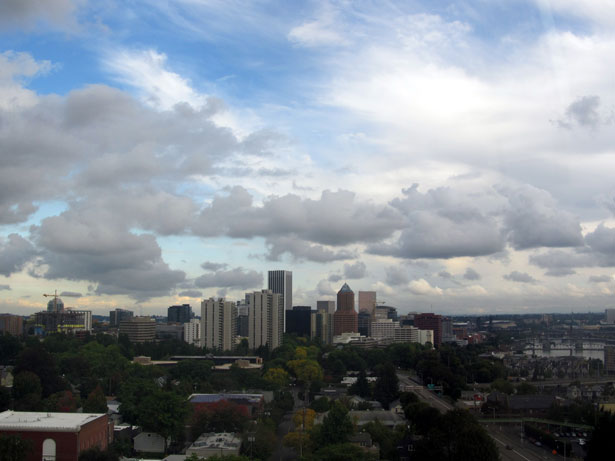 The skyline of Portland, Oregon stretches into a cloudy, blue sky.