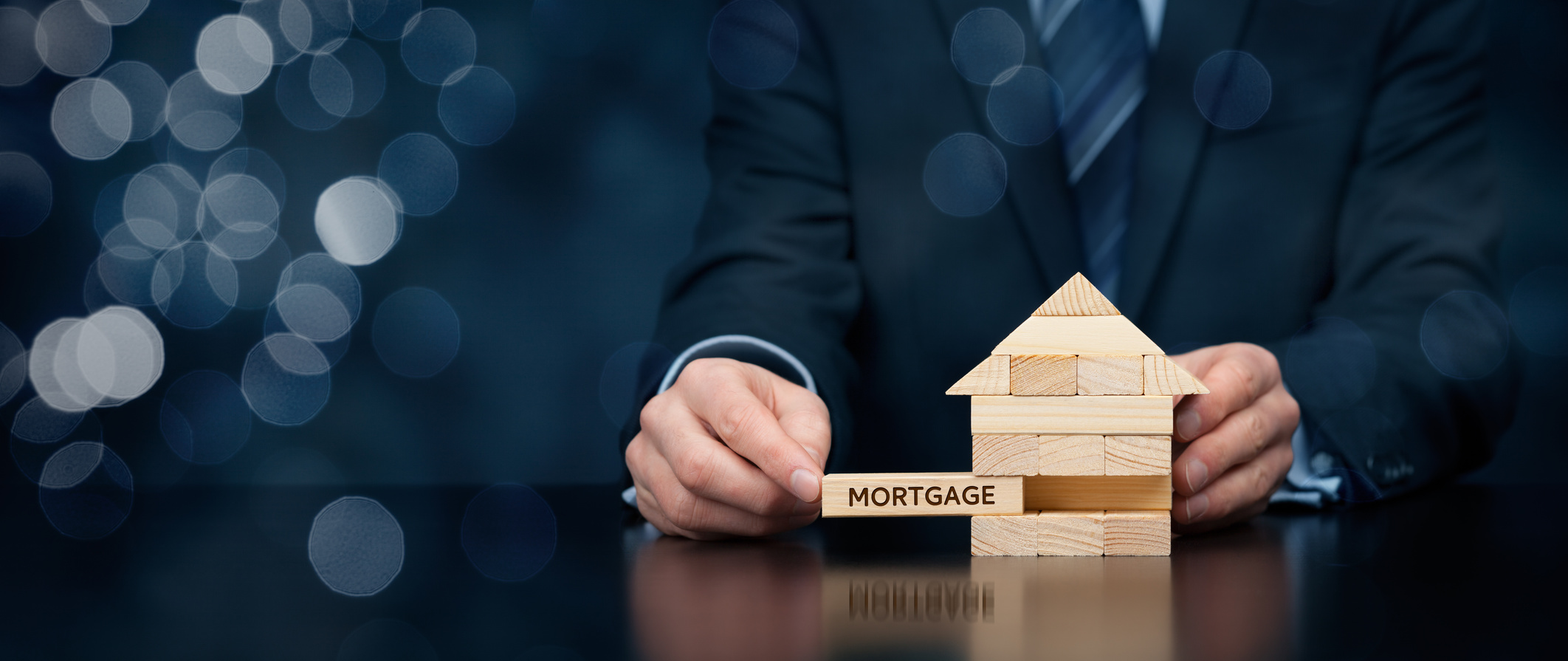 A man in a suit takes a wooden block that says mortgage on it out of a house.