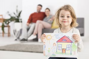 Girl holds house picture by parents on couch.
