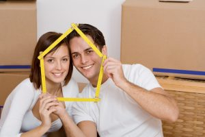 A nice couple holds up a house of Popsicle sticks